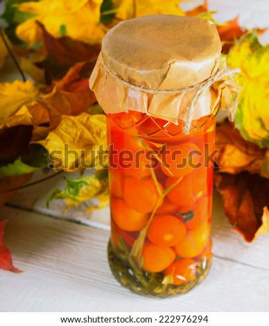 Autumn concept. Preserved food in glass jar on a wooden board. Marinated tomatoes