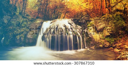 Autumn creek woods with yellow trees foliage and rocks in forest mountain.Filtered image: vintage effect. - stock photo