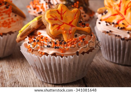 Autumn cupcakes decorated with cream and leaf on a table close-up. horizontal
