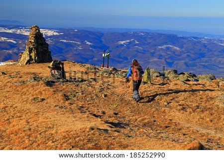 Autumn day on the mountains, with hiker heading to large rock pile
