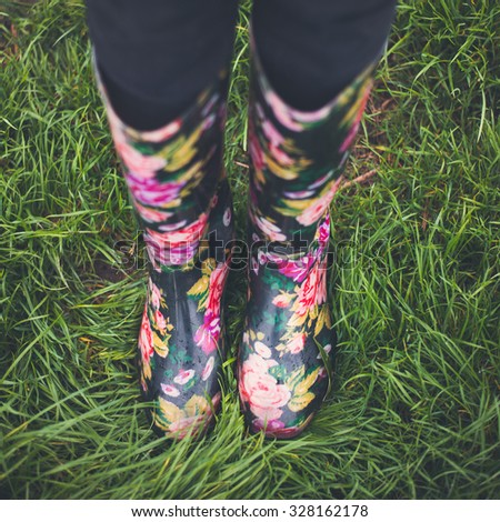 Autumn fall concept with green grass and rain boots outside. Close up of woman feet walking in rainboots. - stock photo