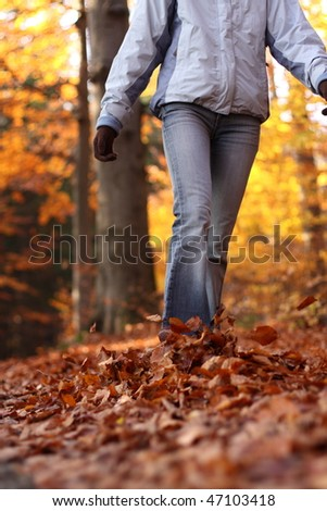 Autumn / Fall - young woman walking in forest in lovely fall colors - stock photo