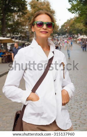 Autumn fashion close up portrait of Attractive fashionable middle-aged woman standing in a street looking thoughtfully at the camera with a charming friendly smile,wearing white jacket,jeans and bag. - stock photo