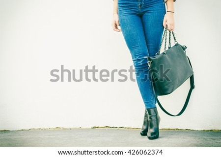 Autumn fashion outfit. Fashionable woman long legs in denim pants black stylish high heels shoes and handbag outdoor on city street - stock photo