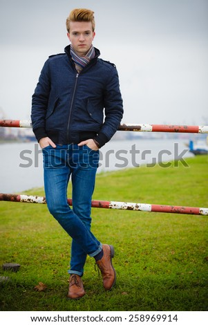 Autumn fashion. Young handsome man model in full length casual style hair styling outdoor against overcast sky, cold autumnal foggy day - stock photo