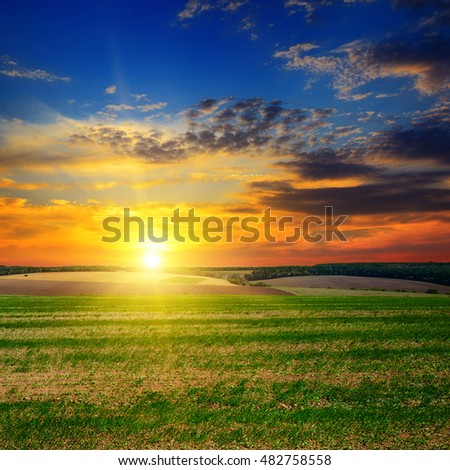 autumn field and evening sunset on the cloudy sky