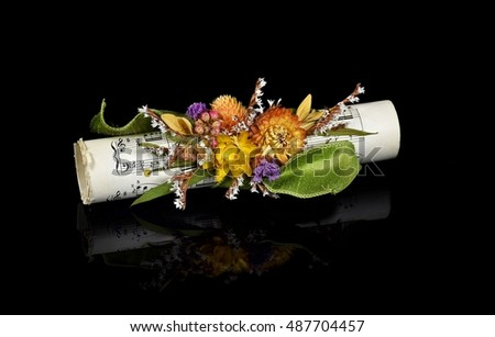 autumn floral bouquet on rolled sheet music on black reflection
