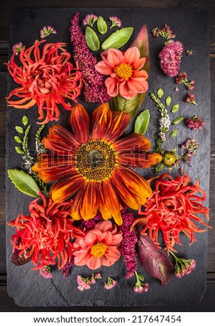 autumn flowers composition with  sunflower, dahlias  and herbs on  dark table , floral background - stock photo