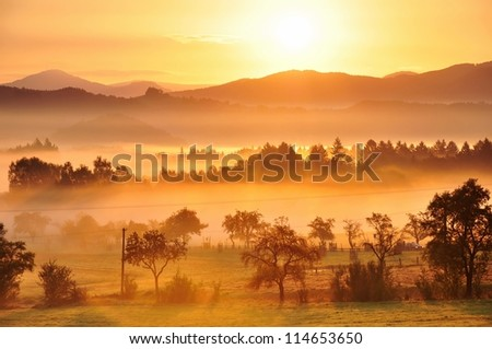 Autumn fog and the beautiful morning sun in a landscape - stock photo
