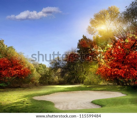Autumn Foliage at the Golf Course - The sun shines on a putting green and lake at a golf course in Autumn. - stock photo