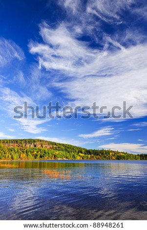 Autumn forest and lake with dramatic sky in Algonquin Park, Canada - stock photo