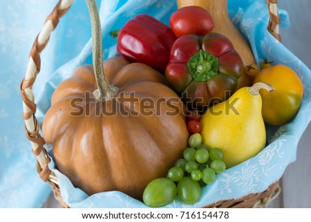 Autumn fresh pumpkin, grape, pear, bell pepper, tomato closeup - homegrown harvest in basket