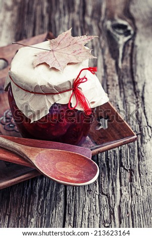 Autumn fruit and berry jam on wooden background