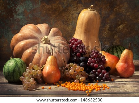 Autumn fruits and gourds, watermelons, grapes, buckthorn on a rustic wooden table - stock photo