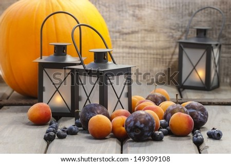 Autumn fruits and traditional lanterns on wooden table. Seasonal decoration. - stock photo