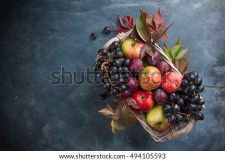 Autumn fruits and vegetables in basket on wooden background, selective focus, autumn nature concept