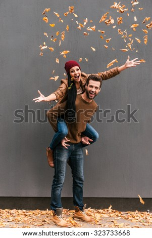 Autumn fun. Full length of handsome young man piggybacking his girlfriend throwing orange fallen leaves an smiling with grey wall as background  - stock photo