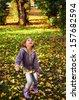 Autumn fun, happy child - lovely girl has a fun in autumn leaves - stock photo
