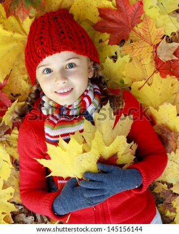Autumn fun - lovely girl has a fun in autumn leaves,  happy child - stock photo