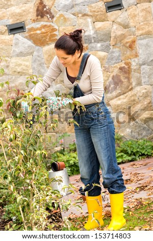 Autumn gardening young woman clipping bush veranda yard hobby