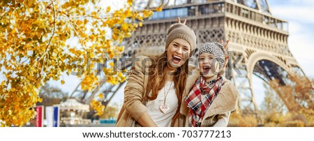 Autumn getaways in Paris with family. Portrait of happy mother and child travellers on embankment in Paris, France having fun time