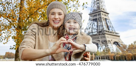 Autumn getaways in Paris with family. Portrait of happy mother and daughter tourists on embankment near Eiffel tower in Paris, France showing heart shaped hands