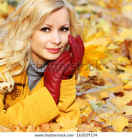 Autumn Girl. Fashion Blonde Beautiful Woman with Maple leaves in hand. Looking at camera. Fall park  - stock photo