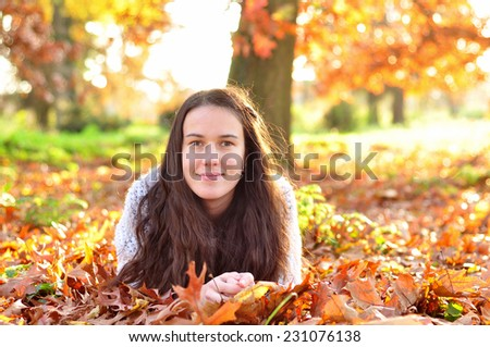 Autumn girl in park laying on leaves