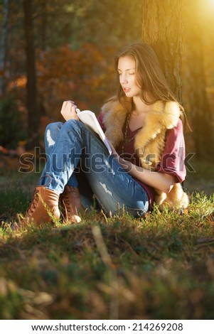 Autumn girl reading book when in the woods