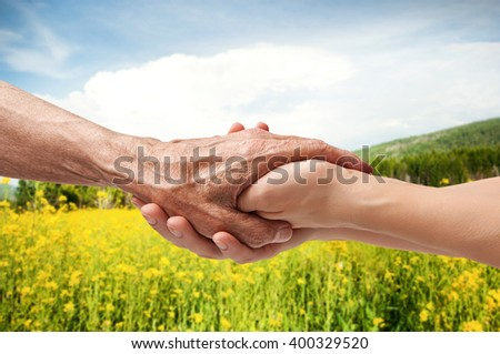 Autumn. Hands of an elderly senior holding the hand of a woman - stock photo
