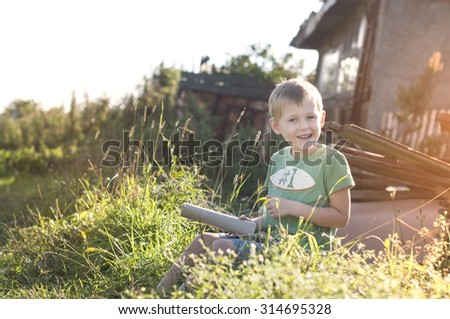 autumn, happy cheerful funny little child sitting on grass in countryside on sunset - stock photo