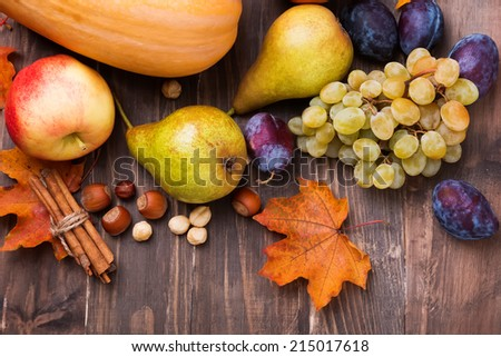 Autumn harvest. Pears, apple, grapes and yellow leaves on the wooden table - stock photo
