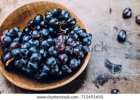 Autumn Harvest Product Food. Bunches of fresh ripe red grapes in a wooden bowl on a metal textural surface background. Dark grapes, blue grapes, wine grapes. Copy space, top view