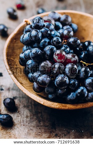 Autumn Harvest Product Food. Wooden Bowl of fresh ripe red grapes on a metal textural surface background. Dark grapes, blue grapes, wine grapes. Copy space