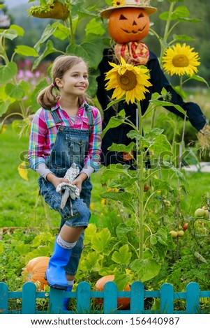 Autumn harvest - Scarecrow and happy girl  in the garden