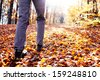 Autumn hiking. Close up of female walking uphill with lots of leaves around - stock photo