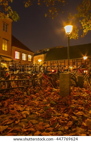 Autumn in Malmo, Sweden. Autumn leaves and bikes at night - stock photo