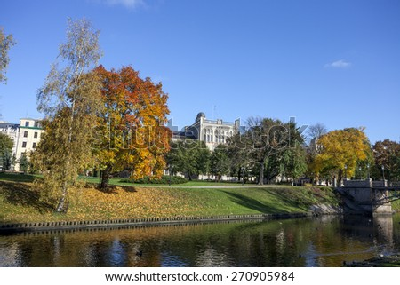 Autumn in Riga, Trees of park, city canal. Central building of University of Latvia in background. - stock photo