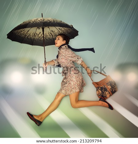 Autumn in the city. Young woman running cross the road at the pedestrian crossing holding umbrella and bag in the rain.  - stock photo