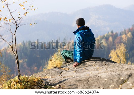 Autumn in the mountains. A tourist sits on a rock and looks at a picturesque valley
