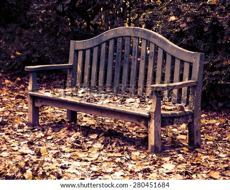 Autumn in the park. Golden leaves on the old wooden bench and on the ground. Love declaration on bench's planks (French and Asian language characters, heart shape). Aged photo. - stock photo