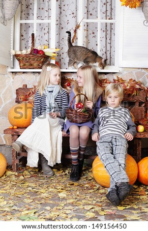 Autumn kids - little boy and girls with pumpkin and leaves - stock photo