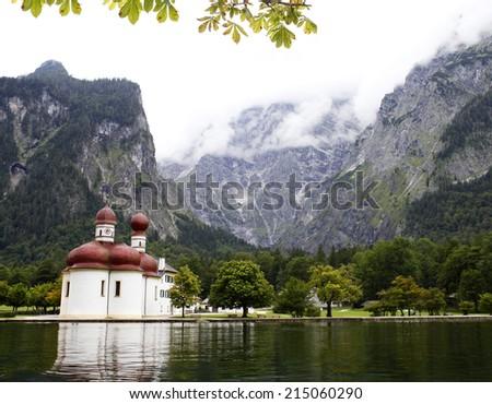 autumn lake konigsee in Alps and St. Bartholomew church - stock photo