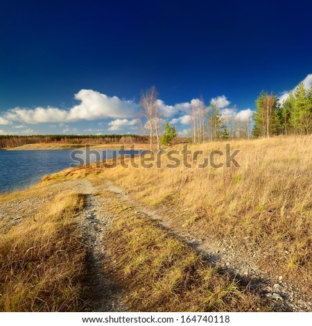 Autumn lake landscape against blue sky - stock photo