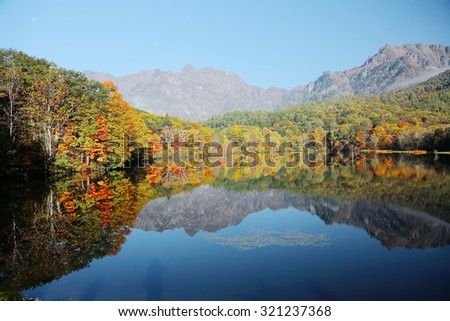 Autumn lake Scenery. Forests of colorful foliage reflecting on the smooth water of Kagami Ike ( Mirror Pond ) with Mountain Togakushi in the distant background ~ Beautiful landscape of Nagano, Japan  - stock photo