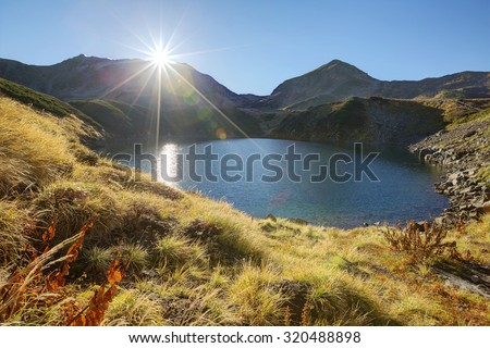 Autumn lake scenery with bright sunlight shining above Mount Tateyama and golden grass around Lake Mikurigaike (a volcanic crater lake), in Murodo Tateyama, Toyama Prefecture Japan - stock photo