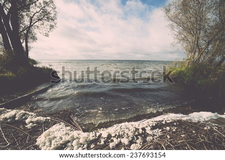 Autumn lake with reflections of trees and clouds - retro, vintage style look - stock photo
