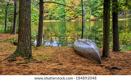 Autumn Lakeshore. Aluminum canoe along the forested lakeshore. Ludington State Park. Ludington, Michigan. - stock photo