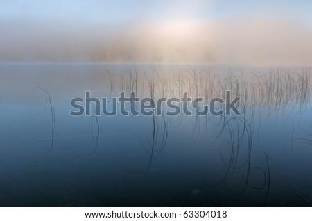 Autumn landscape at dawn of Moccasin Lake in fog, Michigan's Upper Peninsula, USA - stock photo