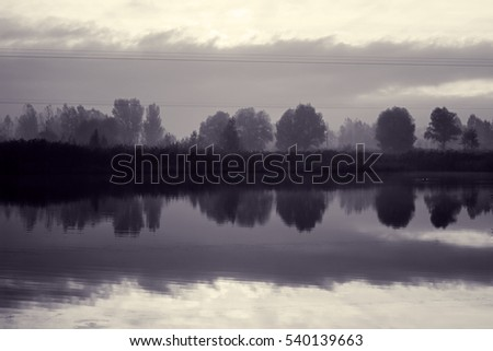 Autumn landscape at sunrise. Silhouettes of trees on bank of river in thick fog on cold morning. Beautiful cloudy sky with rising sun. Cool colors and shades. Toned black and white. Soft warm light
